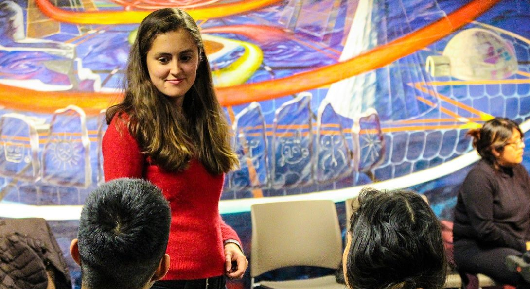 Latina listening to students, has faint smile. Colorful mural in the background.
